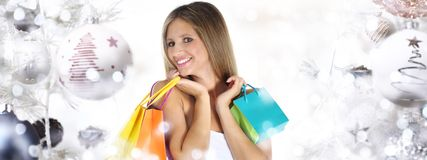 Christmas shopping, smiling woman with bags on christmas ball tr royalty free stock images