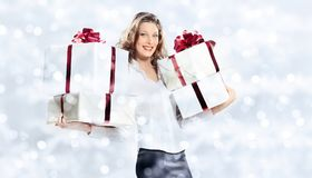 Christmas shopping, smiling woman with gifts packages on blurred. Bright lights background, banner template with copy space Royalty Free Stock Photos