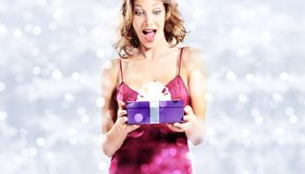 Christmas shopping, surprise woman with gift package on blurred royalty free stock photos