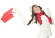Christmas shopping woman with gift bag. Running joyful. Smiling young woman in winter clothes holding red shopping bags. Isolated on white background royalty free stock photos