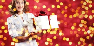 Christmas shopping, woman with gift package on blurred bright li Royalty Free Stock Photo