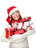 Christmas shopping woman holding gifts. Smiling happy looking up to the side isolated on white background. Cute Santa girl wearing warm sweater and santa hat Stock Images