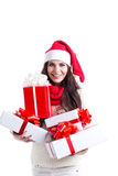 Christmas shopping woman holding many Christmas gifts in her arms wearing santa hat and winter clothing. Stock Photography
