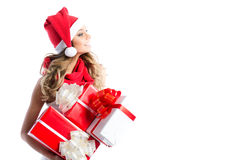 Christmas shopping. Woman in santa hat holding gifts. Stock Photo