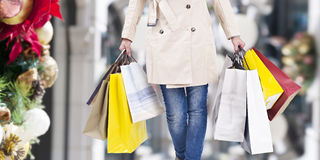 Christmas shopping. Woman walking with shopping bags with christmas background stock image