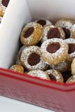 Christmas shortbread thumbprint cookies with strawberry jam powdered with castor sugar in red tin box. Festive cozy atmosphere. Holiday pastry baking concept royalty free stock image