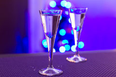 Christmas shot of vodka. Two glasses of vodka with blurry christmas tree background Stock Image