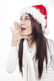 Christmas shout by beautiful woman with Santa hat. Asian woman is shouting because Christmas is near, wearing a santa hat and scarf with white background Stock Photo