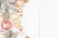 Free Christmas Side Border Of Snowy Branches And Dusty Rose, Gold, And White Ornaments. Over A White Wood Background Royalty Free Stock Images - 162993129