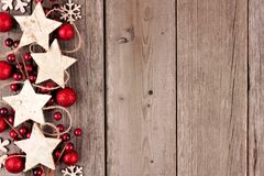 Christmas side border with rustic wood star ornaments and baubles on aged wood stock photo