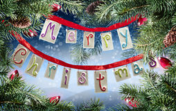 Christmas sign. A tin Merry Christmas sign hanging in pine limbs with a blue mountain backdrop and red ornamental lights Stock Photo