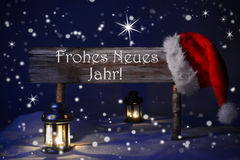 Christmas Sign Candlelight Santa Hat Frohes Neues Means New Year. Wooden Christmas Sign And Santa Hat With Snow. German Text Frohes Neues Jahr Means Happy New Stock Image