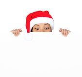 Christmas sign girl. Christmas woman with sign. Very beautiful mixed race asian / caucasian woman with billboard looking surprised down at the sign. Isolated on royalty free stock photo