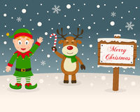 Christmas Sign - Green Elf & Reindeer. A Christmas card with a happy green elf smiling and a cute reindeer holding a candy cane in a snowy scene with a merry Royalty Free Stock Image