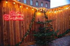 Christmas sign Merry Christmas on a wooden market wall and christhmas tree. Celebration time in winter with beautiful wooden and green decorations Royalty Free Stock Images