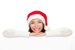 Christmas sign - Santa woman. Showing blank billboard banner sign smiling happy looking at camera. Beautiful cute mixed race Asian Caucasian female model Royalty Free Stock Image