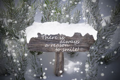 Christmas Sign Snowflakes Fir Tree Text Reason Smile. Wooden Christmas Sign With Snow And Fir Tree Branch In The Snowy Forest. English Quote It Is Always A stock photos