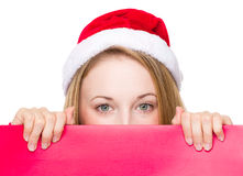 Christmas sign woman peeking over red board Stock Photo