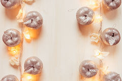 Christmas silver apples decoration and lights burning  on a beige wooden background. Xmas background Royalty Free Stock Photos