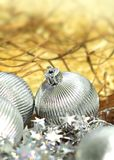 Christmas silver balls. Silver Christmas balls on yellow artistic background royalty free stock photography
