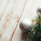 Christmas silver balls, tinsel, fir branches on a wooden background. Christmas concept. Christmas silver balls, tinsel, fir branches on a wooden background Stock Photo