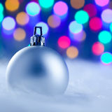 Christmas silver bauble in blurred lights Stock Image