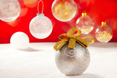Christmas silver bauble with golden loop on snow Stock Images