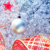 Christmas silver bauble and red ribbon on ice Royalty Free Stock Images
