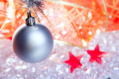 Christmas silver bauble and red ribbon on ice Royalty Free Stock Photos