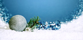 Christmas silver bauble and snow  on blue . Royalty Free Stock Photo
