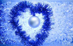 Christmas silver bauble tinsel heart shape. On blue winter ice Stock Photography
