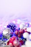 Christmas silver baubles and ornaments against festive lights Royalty Free Stock Photo