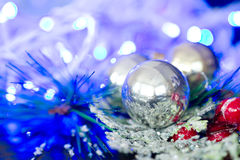 Christmas silver baubles and ornaments against festive lights Royalty Free Stock Photography