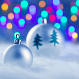 Christmas silver baubles witn tree and lights. Christmas silver baubles witn tree and burred lights background Royalty Free Stock Photography