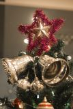 Christmas Silver bell and star hanging on a beautiful Chrismas t. Ree surrounded by red and white shinning ball Royalty Free Stock Images