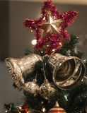 Christmas Silver bell and star hanging on a beautiful Chrismas t. Ree surrounded by red and white shinning ball Royalty Free Stock Photos
