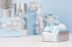 Christmas silver gift box with blue silk ribbon closeup and decorations and gifts in blue. royalty free stock images