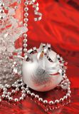 Christmas silver ornament of red background. Close up on a ball christmas ornament with shiny ribbon, beads on a red background royalty free stock images