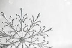 Christmas silver snowflake on abstract white glitter holiday background. Stock Photos