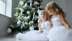 Christmas sisters embrace with artificial snow on hair on background Xmas tree with ornaments