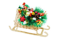 Christmas Sled. Christmas gift. Sled handmade, decorated with tinsel, toys, pine cones and candy. Isolated on a white background Royalty Free Stock Images
