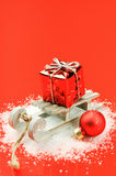 Christmas sleigh with gift on red background Royalty Free Stock Photo