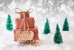 Christmas Sleigh On White Background, 2019, Silver Bokeh Effect. Sleigh Or Sled With Christmas Gifts Or Presents. Snowy Scenery With Snow And Trees. White royalty free stock photos