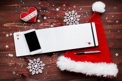 Christmas with smartphone, decoration, notepad and hat. Royalty Free Stock Photography