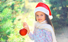 Christmas smiling child little girl in santa red hat with ball near branch tree Stock Photo