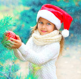 Christmas smiling child little girl in santa red hat holding ball near branch tree Stock Image