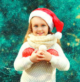 Christmas smiling child little girl in santa red hat with many balls near tree Stock Image