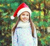 Christmas smiling child little girl in santa red hat over tree Royalty Free Stock Photo