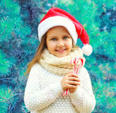 Christmas smiling child little girl in santa red hat with sweet lollipop cane near branch tree Stock Photo