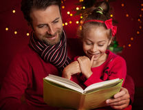 Christmas - smiling father and daughter reading a book Stock Image